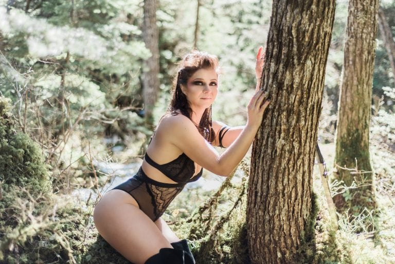 outdoor viking boudoir client sitting on mossy tree in black lingerie while viking sword rests against tree