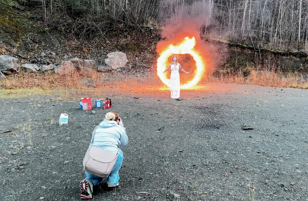 behind the scenes image of photographer taking photo in front of a metal hoop of fire